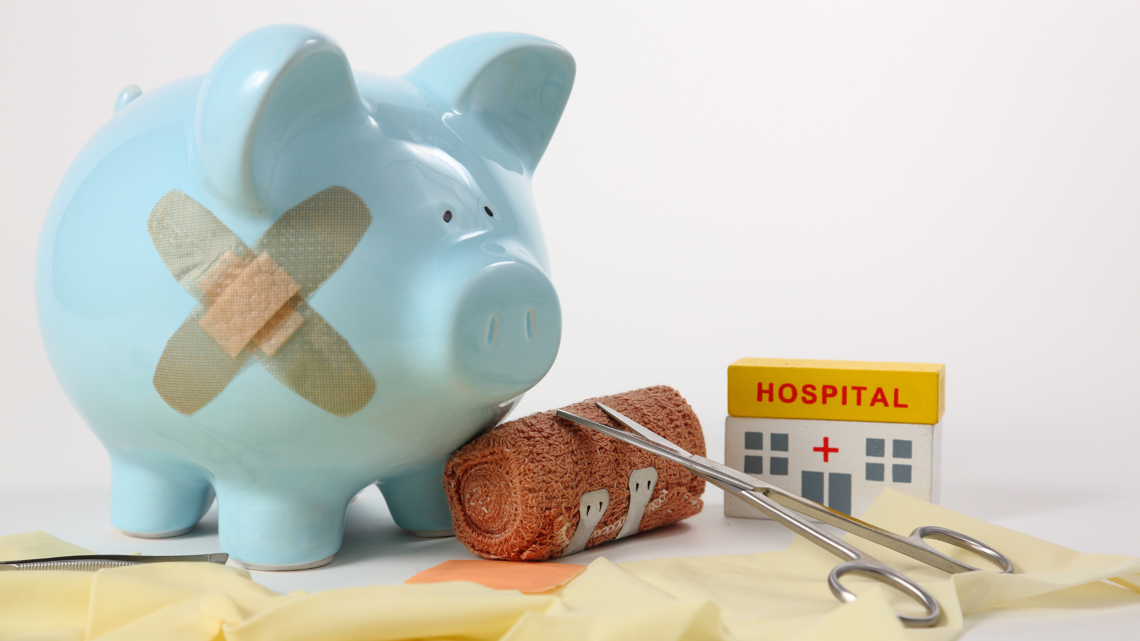 Blue piggy bank with band-aids on its' side. A roll of gauze, surgical scissors, and a small block shaped like a hospital are next to it.