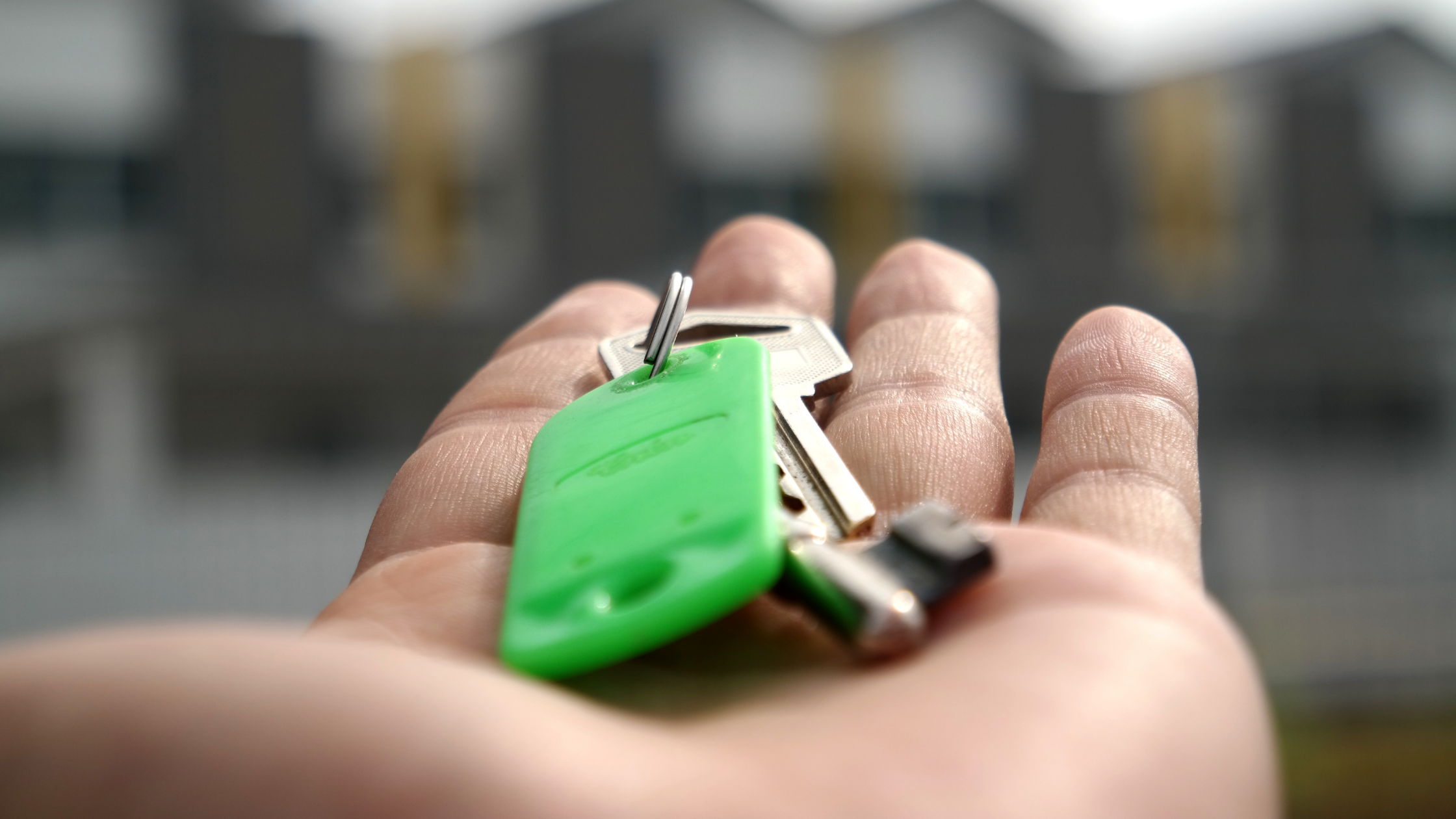 Person holding a set of keys to a house in their outstretched hand.