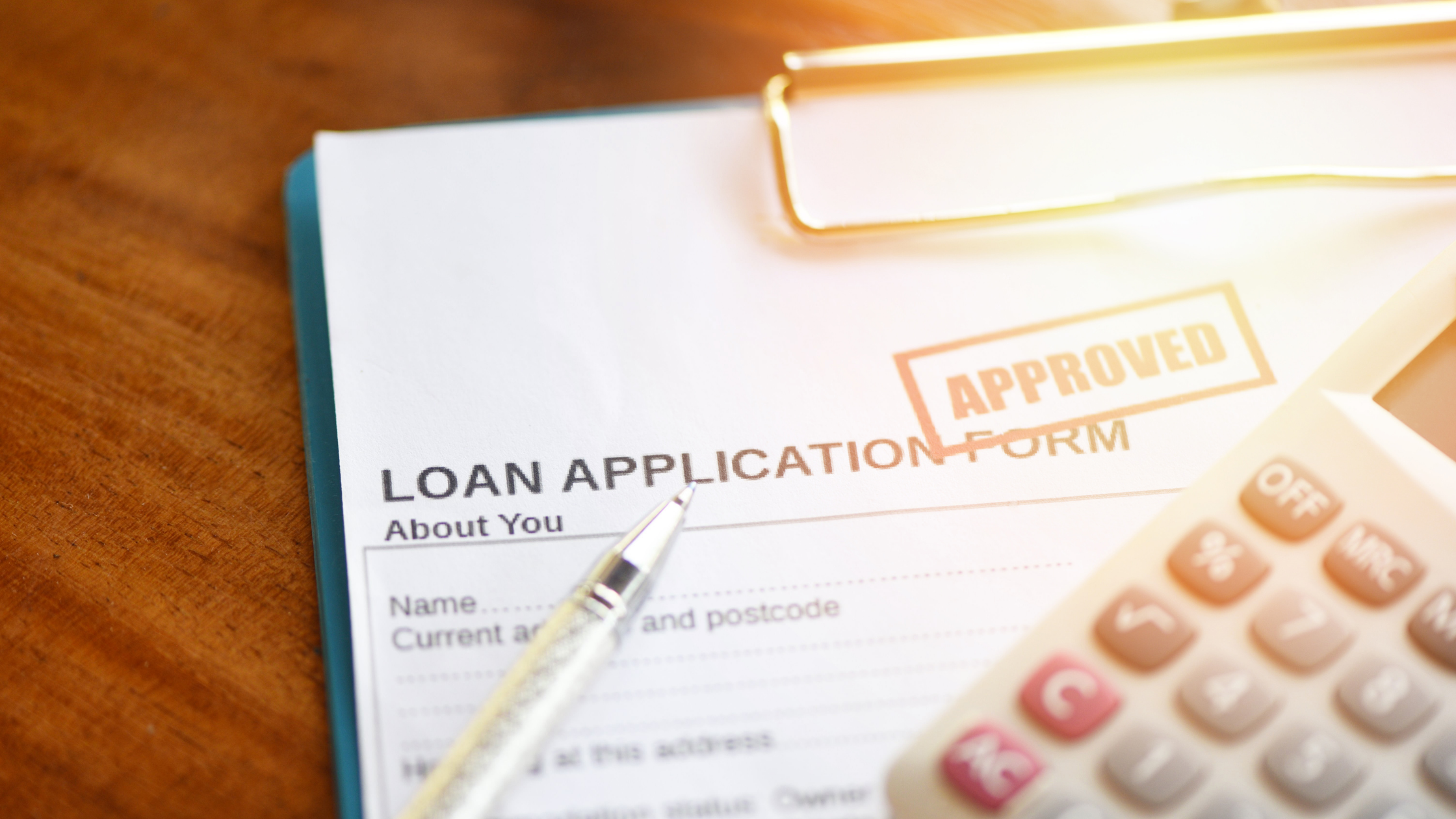 Image of loan application form with a pen and a calculator.