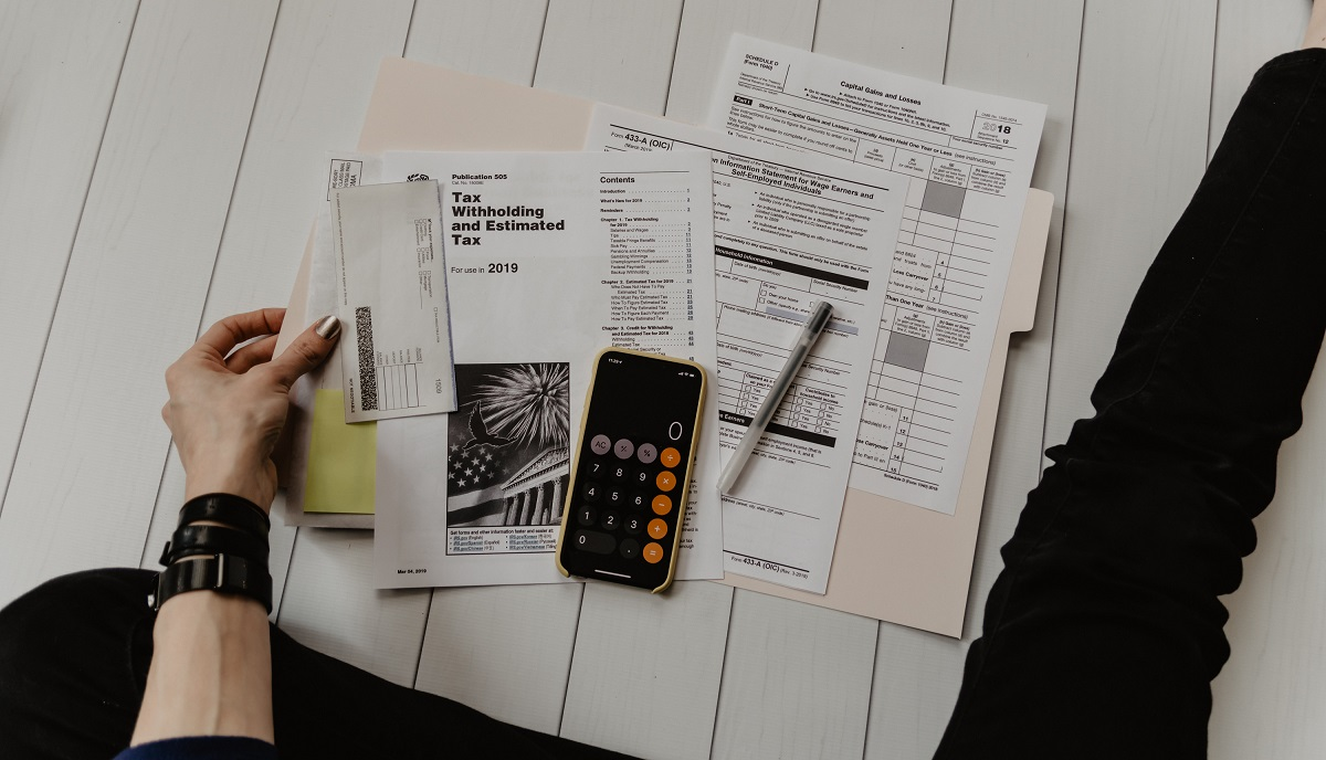 Image of tax documents and calculator. Photo by Kelly Sikkema on Unsplash.