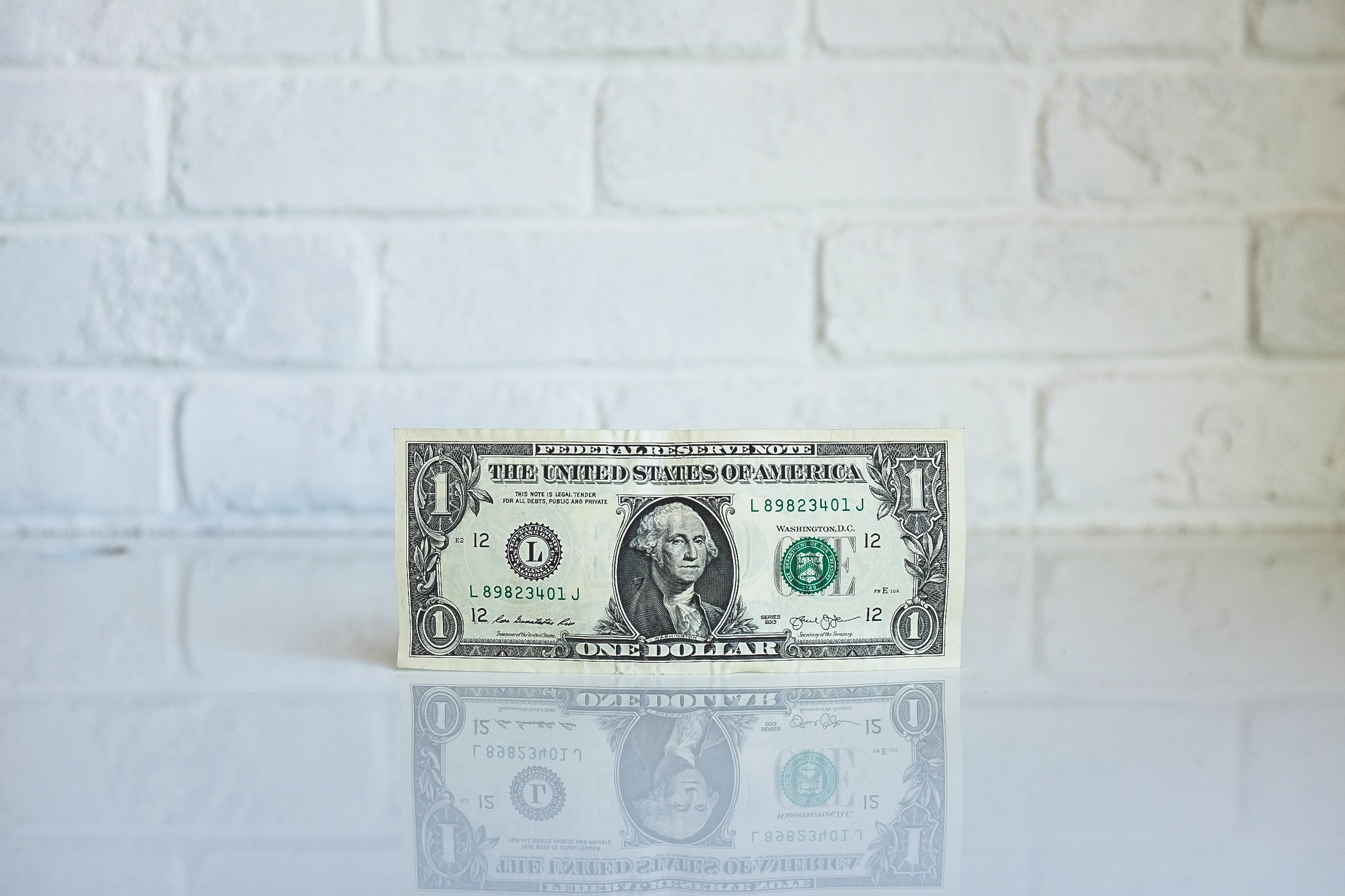 Image of a one dollar bill against a white brick background. Photo by NeONBRAND on Unsplash.
